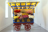 Micheal Landy, Costermonger Stall No.3, 1991, Life sized Flowerstall (steel, wood, tarpaulin, lighting fixtures,flower buckets) & fresh flowers., 239 x 183 x 122 cm, Collection Irish Museum of Modern Art, Loan, Weltkunst Foundation, 1996